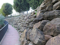 Retaining wall from rough granite blocks. In residential street in Alora, Andalucia stock images