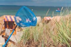 Rete blu della mano sulla spiaggia Sedie di legno coperte sulla spiaggia sabbiosa nel fondo Travemunde, Germania Fotografie Stock