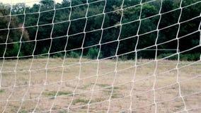 Rete di calcio Griglia di calcio vista attraverso la rete di calcio sul portone opposto Campo di football americano rurale archivi video