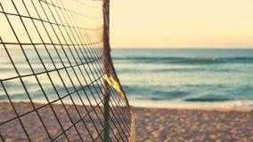 Rete di pallavolo e bella alba sulla spiaggia stock footage