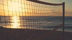 Rete di pallavolo e bella alba sulla spiaggia archivi video