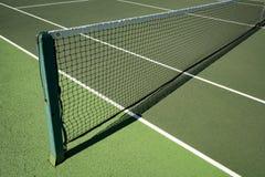 Rete di tennis messa insieme attraverso il campo da tennis hardwearing artificiale Fotografie Stock Libere da Diritti