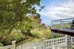 Rete fissa bianca e piattaforma del cortile posteriore con la vista dell'acqua. Fotografie Stock Libere da Diritti