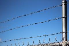 Rete fissa del filo contro cielo blu Fotografie Stock Libere da Diritti