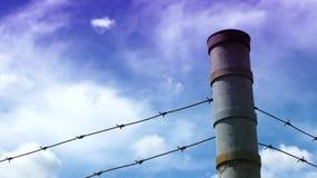 Rete fissa di Barbwire su un cielo blu Fotografia Stock Libera da Diritti