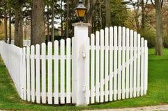 Rete fissa di picchetto bianca con il cancello fotografia stock