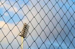 Rete nera di calcio con il fondo del palo del riflettore e del cielo blu Fotografia Stock