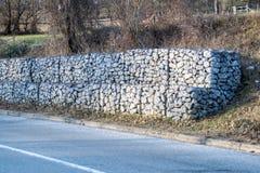 Retendo a parede de pedra ao lado da estrada Malha de aço da parede do gabion Foto de Stock Royalty Free