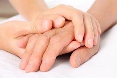 Retenir la main aînée donnant l'aide Image libre de droits