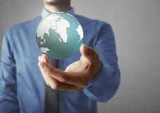 Retenir un globe rougeoyant de la terre dans des ses mains Image de la terre fournie Photos stock