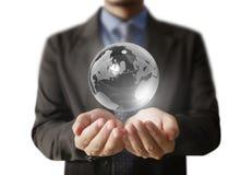 Retenir un globe rougeoyant de la terre dans des ses mains Image de la terre fournie Photographie stock libre de droits