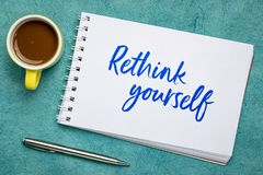 Rethink yourself - advice or reminder note. Handwriting in a spiral art sketchbook against against textured bark paper with a cup of coffee royalty free stock photo