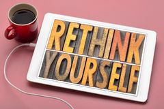 Rethink yourself inspirational word abstract. Rethink yourself word abstract in vintage letterpress wood type blocks on a digital tbalet with a cup of coffee royalty free stock photo