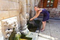 Rethymno, île Crète, Grèce, - 1er juillet 2016 : La jeune femme boit l'eau froide claire de la fontaine de Rimondi dans la pièce  Image stock