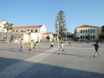 Rethymno, Греция - 15-ое июня 2017: подростки мальчиков различных национальностей играя футбол на солнечном вечере в центре город стоковые фото
