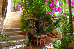 RETHYMNO, CRETA 23 DE JULHO: Rua estreita com um restaurante local em julho 23,2014 na cidade de Rethymno na Creta, Grécia Imagem de Stock Royalty Free