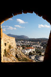 Rethymno through the Fortezza window. Cretian city of Rethymno and surrounding mountains viewed through a Fortezza ancient fort window Royalty Free Stock Photo