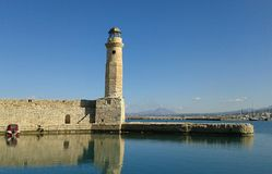 Rethymno Harbour lighthouse. Old brick lighthouse. Entrance to Rethymno Habour. Crete. Greece. Reflection in water Royalty Free Stock Images