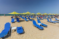 Rethymno, Island Crete, Greece, - July 1, 2016: City beach with people and blue daybeds with green umbrellas Stock Photos