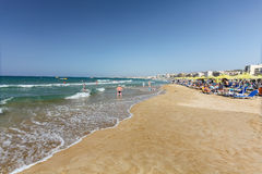 Rethymno, Island Crete, Greece, - July 1, 2016: City beach with people and blue daybeds with green umbrellas Stock Images