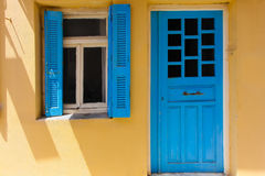 Rethymno, Island Crete, Greece, - June 23, 2016: Traditional Greek house with window with blue shutters and wood door Royalty Free Stock Photos