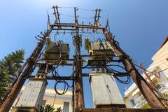 Rethymno, isola Creta, Grecia, - 23 giugno 2016: Palo di potere ad alta tensione con con molti cavi ed alcuni transformators sul Fotografie Stock