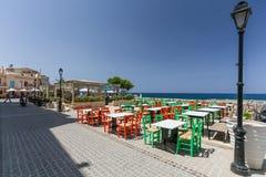 Rethymno, wyspa Crete, Grecja, - Lipiec 1, 2016: Widok kawiarnia która lokalizuje blisko bulwaru Mediter z kolorów krzesłami Fotografia Royalty Free