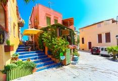 Rethymnon, Insel Kreta, Griechenland, - 1. Juli 2016: Angenehmes kretisches kleines Café mit Blumen draußen mit Anzeige auf dem g Lizenzfreies Stockbild