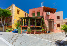 Rethymnon, Insel Kreta, Griechenland, - 1. Juli 2016: Angenehmes kretisches kleines Café mit Blumen draußen mit Anzeige auf dem g Stockfotografie