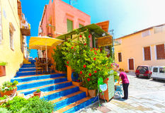 Rethymnon, Island Crete, Greece, - July 1, 2016: Cosy cretan small cafe with flowers outside with and waitress is putting a menu o Stock Photo