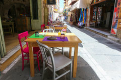 Rethymnon, Island Crete, Greece, - June 23, 2016: Tables and chairs of cafe are on the narrow street of Rethymnon part of Old Tow. Tables and chairs of cafe are Stock Photography
