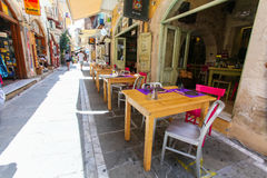 Rethymnon, Island Crete, Greece, - June 23, 2016: Tables and chairs of cafe are on the narrow street of Rethymnon part of Old Tow. Tables and chairs of cafe are Royalty Free Stock Images