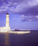 Rethymnon lighthouse. In Crete, Greece, in the late afternoon light with a cargo ship in the background Stock Image