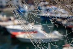 Reti da pesca contro le barche in porto, fuoco selettivo Fotografia Stock