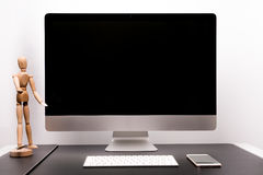 Retina display with keyboard, mouse, smart phone and wood man Royalty Free Stock Image