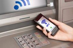 Retirando o dinheiro atm com telemóvel um terminal de NFC Imagens de Stock