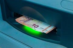 Retire el dinero de la atmósfera 10 billetes de banco euro en la máquina de la atmósfera imagen de archivo libre de regalías