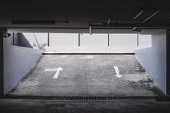Retire a entrada do estacionamento subterrâneo do carro com sinal de estrada das setas Fotos de Stock Royalty Free
