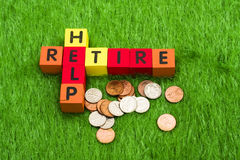 Retire and Help. Alphabet blocks spelling retire and help with coins Stock Photo