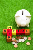Retire and Help. Alphabet blocks spelling retire and help with a piggy bank Stock Photo