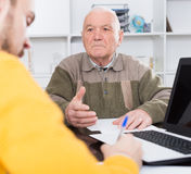 Retired and agent sign insurance contract. Old men and agent sign life and health insurance contract in office stock images