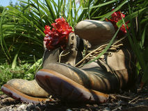Retired boots. Old work boots put to good use in the summer, planted in a garden with red begonia flowers Stock Image