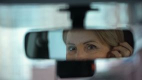 Retired business woman looking at her reflection in rear view mirror, driver. Stock footage stock footage