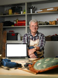 Retired carpenter with laptop. Portrait of retired craftsman sitting behind the laptop screen in his workshop and looking at camera.  Small business Stock Photography