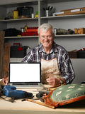 Retired carpenter with laptop. Portrait of retired craftsman sitting behind the laptop screen in his workshop and looking at camera.  Small business Royalty Free Stock Photos