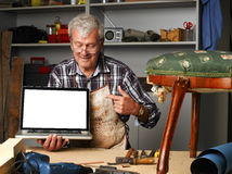 Retired carpenter with laptop. Portrait of retired carpenter points out of laptop screen while sitting in his workshop next to the broken away legged chair Royalty Free Stock Photos