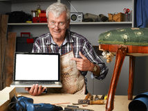 Retired carpenter with laptop. Portrait of retired carpenter points out of laptop screen while sitting in his workshop next to the broken away legged chair Royalty Free Stock Image