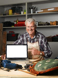 Retired carpenter with laptop. Portrait of retired carpenter points out of laptop screen while sitting in his workshop next to the broken away legged chair Stock Image