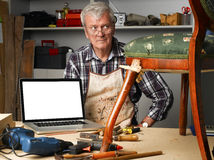 Retired carpenter with laptop. Portrait of retired carpenter points out of laptop while sitting in his workshop next to the broken away legged chair. Small Stock Photography