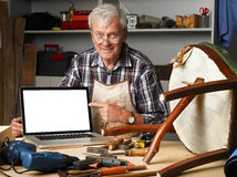 Retired carpenter with laptop. Portrait of retired carpenter points out of laptop while sitting in his workshop next to the broken away legged chair. Small Royalty Free Stock Image